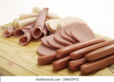 A collection of cold meats, bologna, and vienna sausages on a wooden board on an isolated white studio background