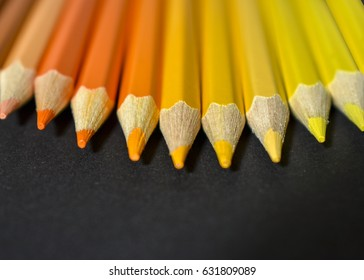 Collection of colored pencils on black background.