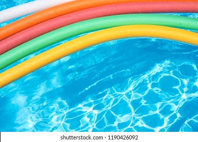 A collection of colorful noodle floatation devices in a pool water.