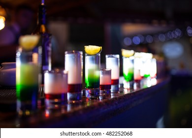 collection of colorful shots with lemon on bar; set of alcohol mini cocktail shooters with lime;