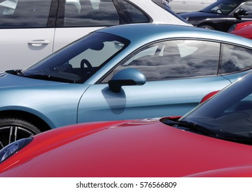 Collection of colorful sport cars parked in car park.