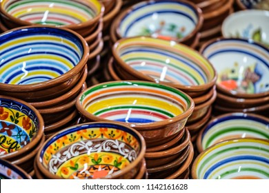 Collection of colorful stoneware bowls with many colors and ornaments