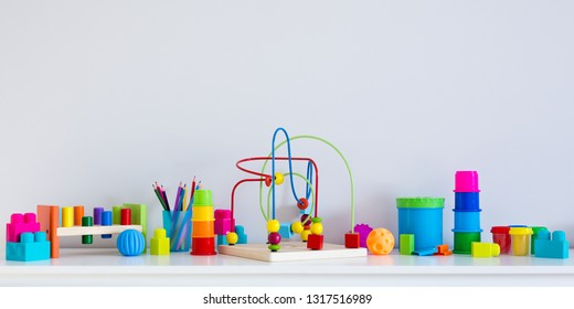 collection of colorful toys and copy space over white wall background