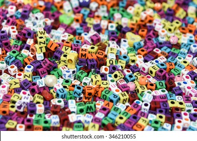 Collection of colourful beads/ blocks to make handmade jewellery/ bracelet names, in Rajasthan, India. heap of multi colored beads in an Indian street shop. Alphabets in kinder garden school for kids