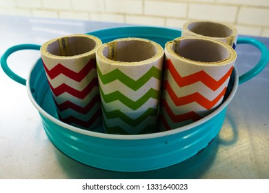 Collection of colourful chevron-striped fabric beer stubby holders on a blue metal tray with handles.