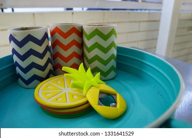 Collection of colourful chevron-striped fabric beer stubby holders on a blue metal tray with yellow lemon coasters and a pineapple shaped beer bottle opener.