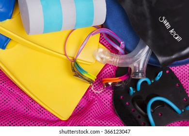 A collection of competitive swimming equipment or gear for swim team spilling out on ground.  Including goggles, fins, and kick board on a pink net swim bag