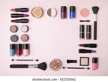 A collection of cosmetic beauty products arranged around a blank space on a pastel pink background, forming a page border