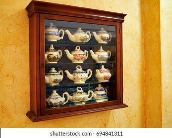 Collection of decorative classical design tea pot in a wooden display cabinet