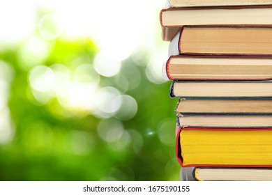 Collection of different books against blurred green background, space for text