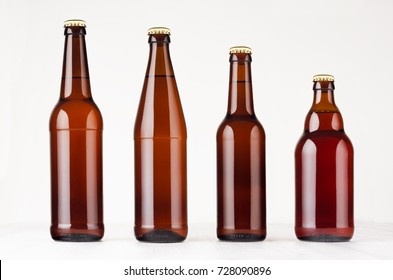 Collection different brown beer bottles, mockup. Template for advertising, design, branding identity on white wood table.