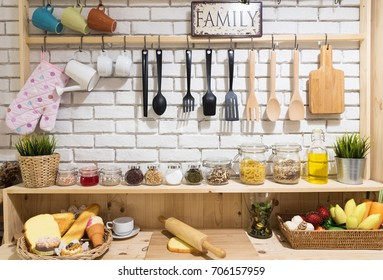 A collection of different ceramics,wooden complement a patterned tiles kitchen behind white brick wall.Kitchenware and tree hanging on the wall. Modern kitchen at home with ,flavoring ,bread and food