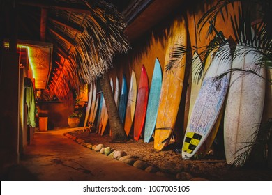 A collection of different colorful surf boards used as a decoration next to a walkway, resting on a wall. Photo taken during the night with a bunch of surfboards on the sand. Surfboards at night