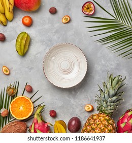 Collection of different multi-colored ripe tropical fruits, empty plates and palm leaves on a gray concrete table with copy space. Flat lay
