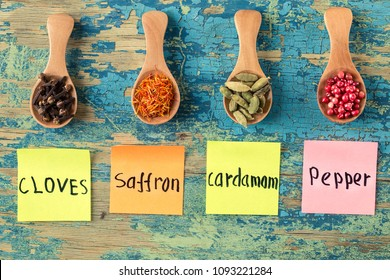 collection of different spices and herbs with labels on rustic wooden background. Assortment of colorful spices. Food ingredients, top view