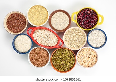 Collection of different types groats, rice, and beans in bowls on a white background. Top view