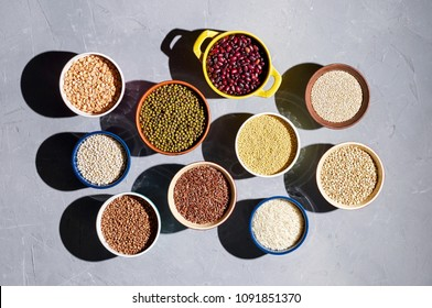 Collection of different types groats, rice, and beans in bowls on a gray background. Top view, closeup, hard light