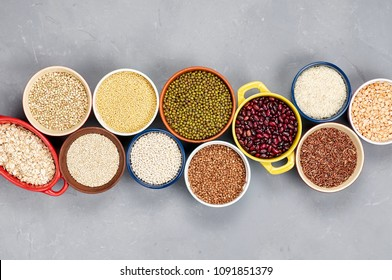 Collection of different types groats, rice, and beans in bowls on a gray background. Top view, copy space