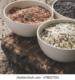 collection of different varieties of rice on wooden rustic background. Selective focus, toning