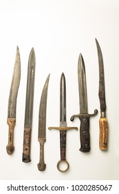 Collection of different vintage knives and daggers with a variety of shapes of blade and hilt or handle laid out in a neat row on white with copy space