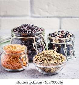 Collection of dry legumes in glass jars on stone background. Selective focus, space for text.