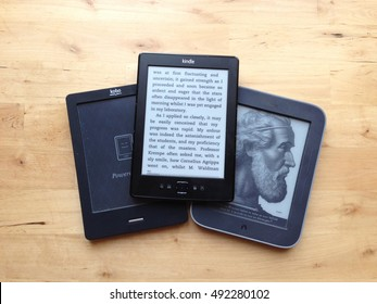 A collection of ebook ereaders, including a Kobo, a Barnes and Noble NOOK and an Amazon Kindle sit on a wooden bench