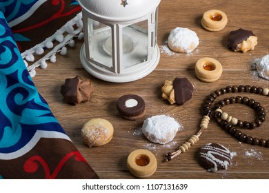 Collection of Eid El Fitr kahk and biscuits - Cookies of El Fitr Islamic Feast on wooden table with Arabian lantern and Islamic Fabrics