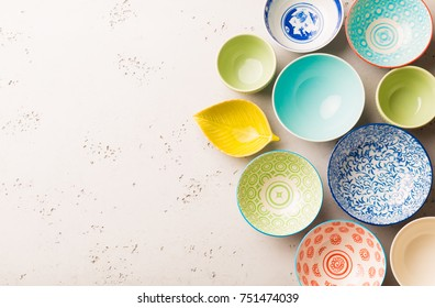 Collection of empty colorful (pastel) decorative ceramic bowls. Layout captured from above (top view, flat lay). Grey stone background with free text space.
