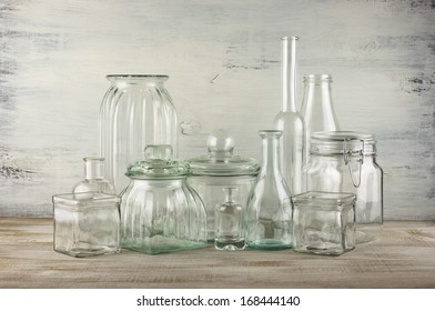 Collection of empty various glassware on vintage wooden background.