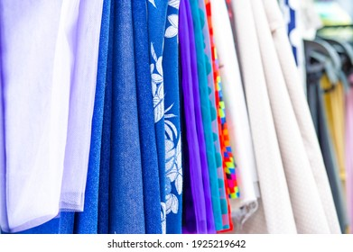 Collection of fabrics at the store counter. View of rolls of fabric in different colors and patterns on the shelves in the store. Texture. background. Template