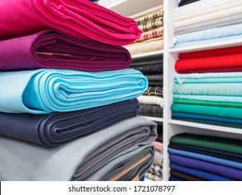 Collection of fashionable bright fabrics in close-up. Samples of different natural fabrics for sewing a fashion collection of clothes. Large selection of fabrics in the store.