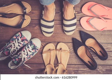 Collection of female shoes on wooden floor. Fashion background