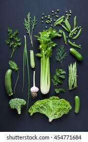 Collection of fresh green vegetables on black rustic background.