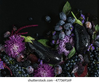 Collection of fresh purple fruit, vegetables and flowers on the black background, top view