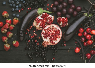 Collection of fresh purple and red fruit and vegetables on the black wooden table vintage color
