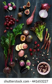 Collection of fresh purple toned vegetables and fruits on dark rustic distressed background, eggplant, beetroot, carrot, fig, aubergine, grapes, radishes, loose lettuce, beans passionfruit, cherries