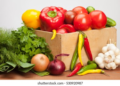 Collection of fresh raw vegetables in a wooden box; sweet and chili pepper, tomato, cucumber, onion, garlic, parsley, dill, leek - organic ingredients for cooking