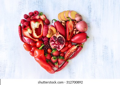Collection of fresh red vegetables and fruits arranged in a heart shape on white rustic background strawberry raspberry pomegranate peppers capsicum chilli potato beans legumes overhead flat lay