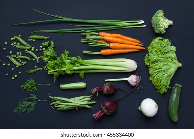 Collection of fresh summer vegetables on black rustic background. Top view