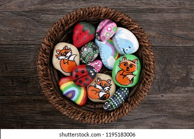 A collection of fun, handpainted, colorful cartoon rocks are together in a wicker basket, on a wooden plank background.