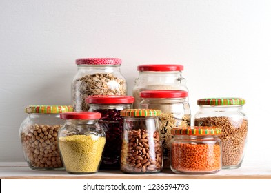 Collection of grain products in storage jars in pantry.