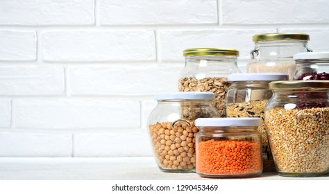 Collection of grain products in storage jars in pantry or on table. Copyspace background.