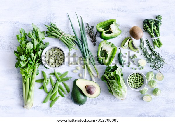 Collection of green produce from farmers market on rustic white background from overhead, broccoli, celery, avocado, brussel sprouts, kiwi, pepper, peas, beans, lettuce,