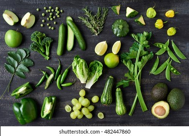 Collection of green vegetables produce on dark background, broccolini, avocado, squash, chilli, grapes part of flat lay overhead set