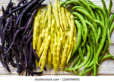 Collection of green, yellow and purple bush beans, opened green peas on wooden white background.