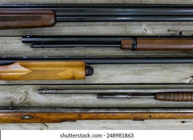 Collection of guns lined up horizontal on wooden background