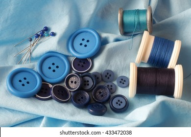 A collection of haberdashery items with a blue theme - buttons, dressmaker's pins and cotton on bobbins. All on a piece of blue fabric.