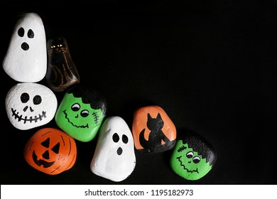 A collection of hand-painted spooky cartoon halloween painted craft rocks featuring ghosts, pumpkins, cats, skeleton, and monsters are bordering a black background with copy-space.