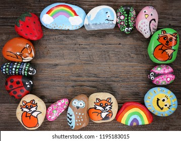 A collection of happy, colorful hand painted cartoon animal rocks are framing a wood plank background.