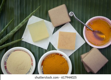 A collection of homemade soaps with their raw materials such as aloe vera, thanaka and tumeric powder and honey with some craft paper-wrapped soap on banana leaf